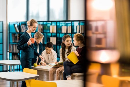 Photo for Selective focus of schoolchildren and librarian talking together in library - Royalty Free Image
