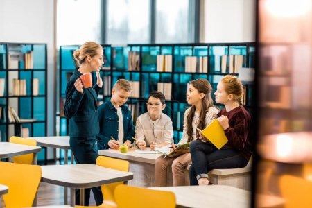 Photo pour Une jeune bibliothécaire et des écolières qui parlent ensemble à la bibliothèque - image libre de droit