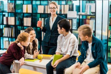 Foto de Joven mujer bibliotecario sostener taza y mirando sonriente escolares en biblioteca - Imagen libre de derechos