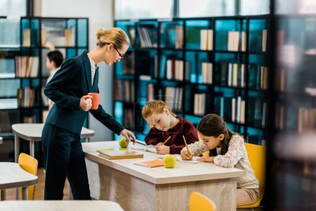 Photo for Young female teacher holding cup and looking at schoolchildren studying in library - Royalty Free Image