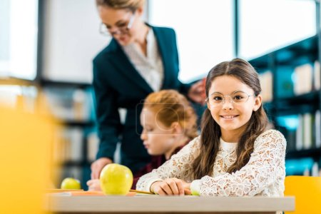 beautiful schoolkid smiling at camera while studying with classmate and teacher in library