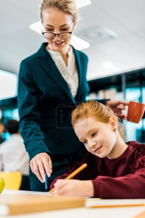 smiling young teacher in eyeglasses looking at schoolgirl studying in library