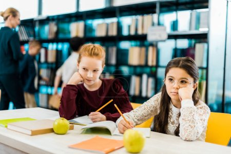 schoolkids writing with pencils and looking away in library