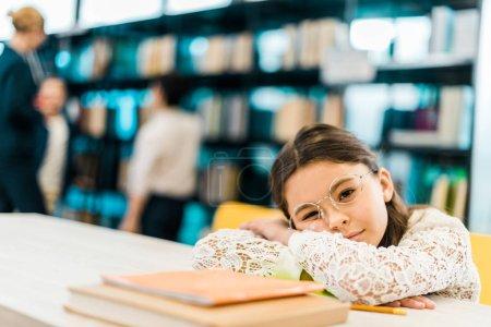 Foto de Colegiala aburrida en espejuelos apoyado en la mesa con libros y mirando a cámara en biblioteca - Imagen libre de derechos
