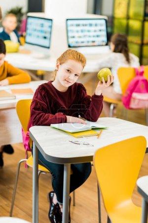 Foto de Adorable potache manteniendo apple y mirando a cámara mientras estaba sentado con compañeros de clase en biblioteca - Imagen libre de derechos