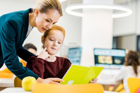 Photo for Young female teacher and adorable schoolkid studying together in library - Royalty Free Image