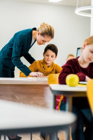 Photo pour Jeune enseignante aidant des écoliers qui étudient dans des bureaux - image libre de droit