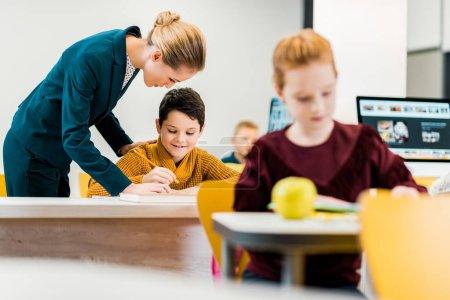 Photo pour Jeune enseignant aidant les écoliers qui étudient dans les bureaux - image libre de droit