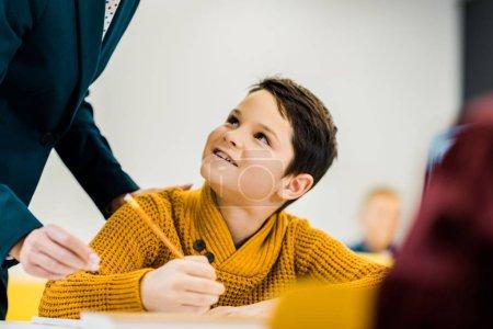 Photo pour Plan recadré de garçon souriant tenant crayon et regardant enseignant - image libre de droit
