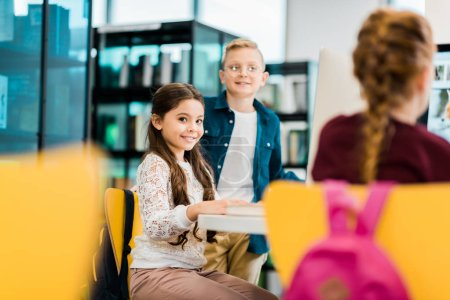 Photo for Cute smiling schoolchildren studying with desktop computers in library - Royalty Free Image