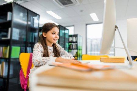 Foto de Adorable potache sonriente con computadora de escritorio en la biblioteca - Imagen libre de derechos