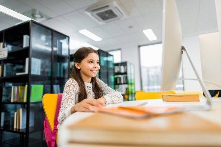 Photo pour Adorable écolière souriante utilisant un ordinateur de bureau dans la bibliothèque - image libre de droit