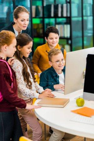Photo pour Écoliers mignons et bibliothécaire en utilisant l'ordinateur ensemble dans la bibliothèque - image libre de droit
