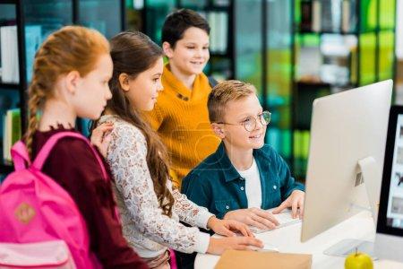 Photo pour Les écoliers souriants utilisant l'ordinateur de bureau ensemble dans la bibliothèque - image libre de droit