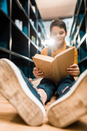 selective focus of schoolboy reading book and sitting on floor in library