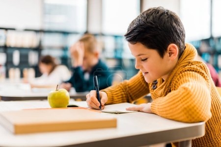 Photo for Smiling boy writing with pen while studying with classmates in library - Royalty Free Image