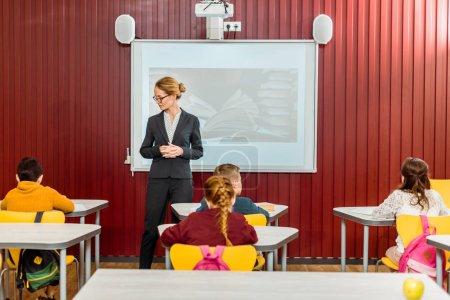 Photo pour Jeune bibliothécaire exposé et en regardant les collégiens assis à un bureau - image libre de droit