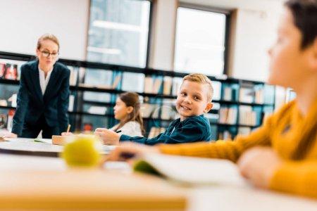 Photo pour Enseignant regardant les écoliers qui étudient dans les bureaux de la bibliothèque - image libre de droit