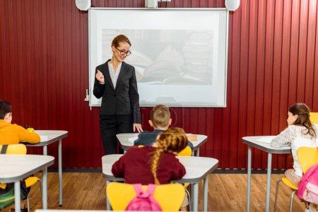 Photo pour Jeune bibliothécaire souriant faisant une présentation et regardant les écoliers prendre des notes - image libre de droit