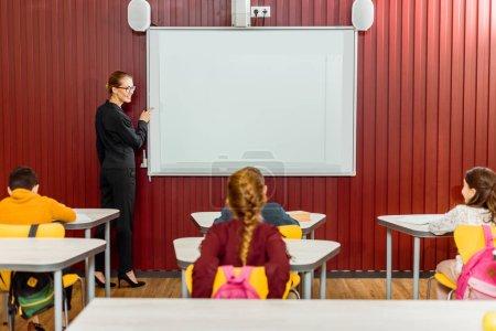 Photo pour Souriant professeur pointant sur tableau blanc interactif et en regardant de collégiens - image libre de droit