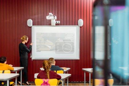 Photo pour Une présentation à tableau blanc interactif aux écoliers de bibliothécaire - image libre de droit