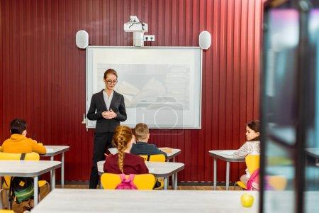 Photo pour Vue arrière du collégiens assis à un bureau et bibliothécaire présentation - image libre de droit