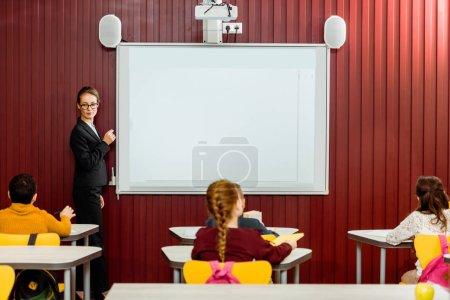 back view of schoolchildren sitting at desks and teacher making presentation at whiteboard