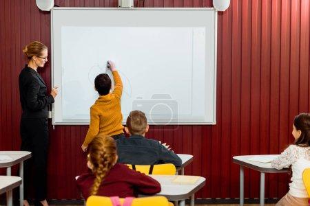Photo pour Vue arrière du garçon au cours de la leçon d'écriture sur tableau blanc interactif - image libre de droit