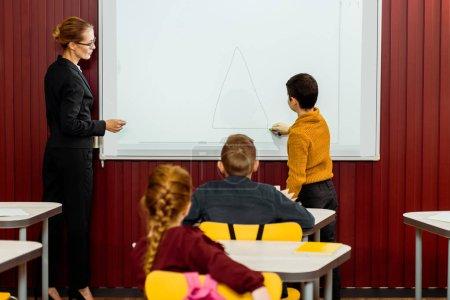 Photo pour Vue arrière du collégiens et enseignants étudie avec tableau blanc interactif derrière - image libre de droit