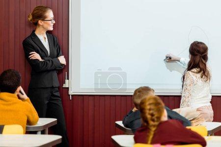 Photo pour Souriante jeune enseignante regardant enfant écrit sur le tableau blanc interactif - image libre de droit