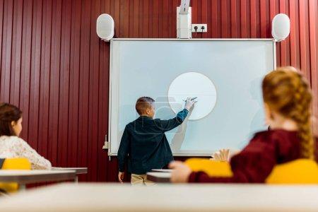 Photo pour Collégiens en regardant garçon une présentation à tableau blanc interactif - image libre de droit