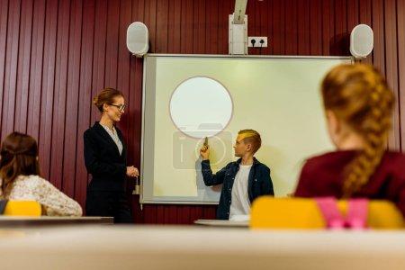 Photo pour Enseignants et collégiens regardant garçon une présentation à tableau blanc interactif - image libre de droit