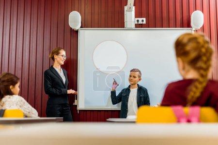 Photo pour Enseignant et élèves regardant garçon une présentation à tableau blanc interactif - image libre de droit