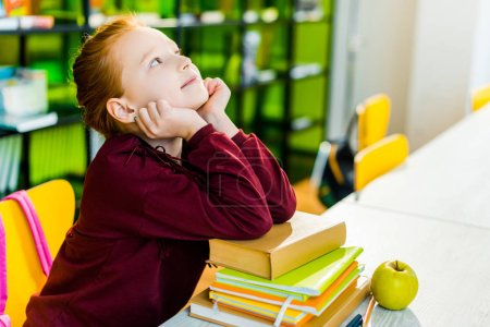 adorable schoolgirl sitting at desk with books and looking up in library