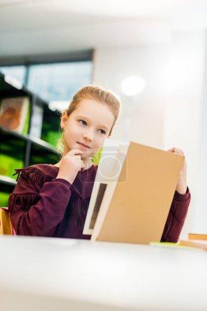 Photo for Beautiful schoolgirl sitting at desk and reading book in library - Royalty Free Image