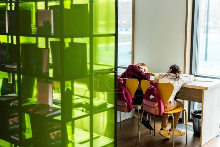 back view of bored schoolgirls lying on table in library
