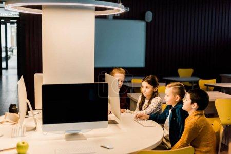 Foto de Adorables niños sentados y utilizando el ordenador de sobremesa juntos en biblioteca moderna - Imagen libre de derechos