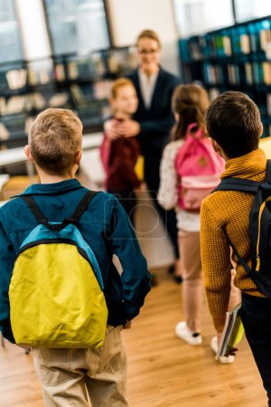 back view of kids with backpacks visiting library together