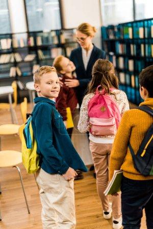 Photo pour Vue arrière des écoliers avec sacs à dos debout avec bibliothécaire à la bibliothèque - image libre de droit