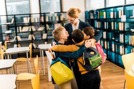 Photo pour Heureux écoliers avec sacs à dos étreignant bibliothécaire dans la bibliothèque - image libre de droit