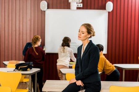 Photo pour Songeur jeune professeur assis sur la table en se tenant debout écoliers près de tableau blanc interactif derrière - image libre de droit