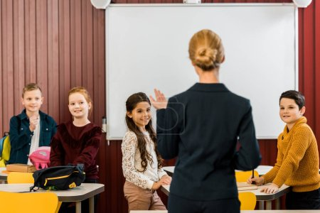 Photo for Back view of young teacher talking with smiling schoolkids - Royalty Free Image