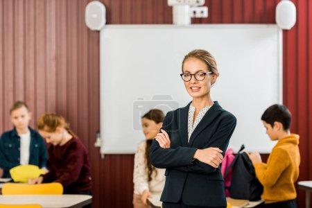 Photo pour Lunettes de vue belle jeune enseignant permanent avec croisé les bras et souriant à la caméra tout en enfants emballage sacs à dos derrière - image libre de droit
