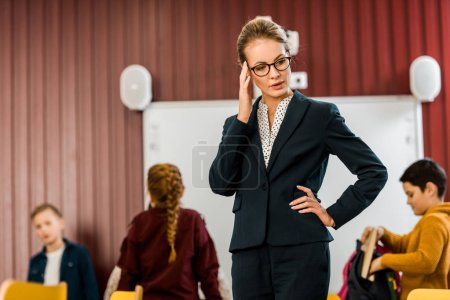 young female teacher in eyeglasses looking down while schoolkids standing behind