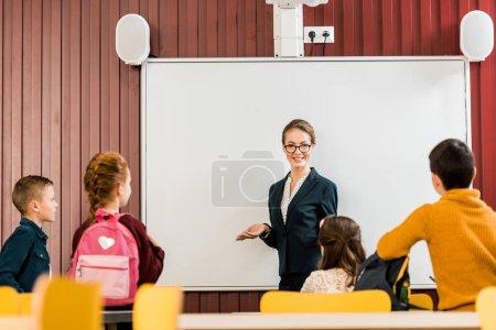 Photo pour Souriante jeune institutrice fait exposé aux écoliers - image libre de droit
