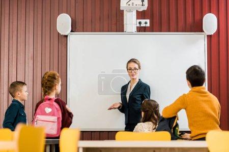 Photo pour Jeune enseignant exposé aux collégiens mignon avec sacs à dos - image libre de droit