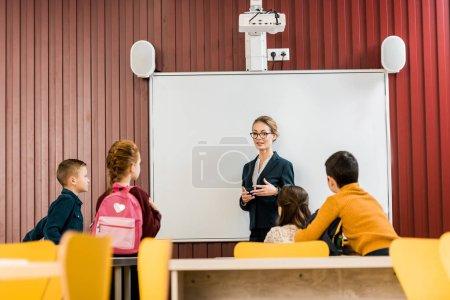 Photo pour Jeune enseignant permanent près de tableau blanc interactif et en regardant les collégiens avec sacs à dos - image libre de droit