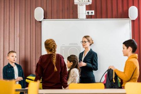 Photo pour Jeune enseignant permanent près de tableau blanc interactif et en regardant les écoliers avec sacs à dos - image libre de droit