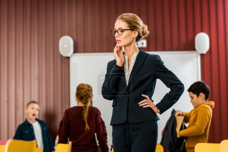 Foto de Bella joven profesora en gafas mirando a escolares estando detrás - Imagen libre de derechos
