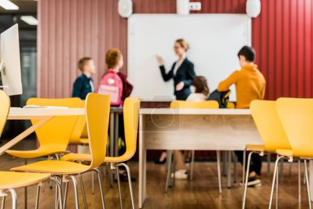 Photo pour Chaises et bureaux sur le premier plan et d'enfants qui cherchent à l'enseignant au tableau blanc interactif derrière - image libre de droit